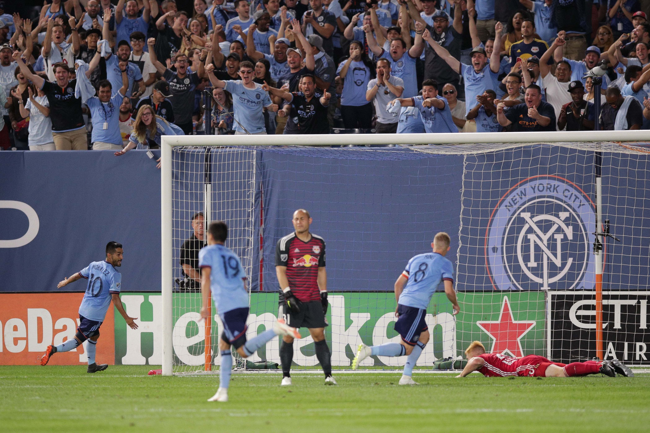 Jul 8, 2018; New York, NY, USA; New York City FC midfielder Maximiliano Moralez (10) celebrates his goal with midfielder Alexander Ring (8) in front of New York Red Bulls forward Bradley Wright-Phillips (99) and defender Tim Parker (26) during the second half at Yankee Stadium. Mandatory Credit: Vincent Carchietta-USA TODAY Sports